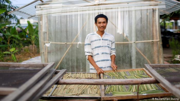 Tran Minh Tien stands behind a drying rack filled with grass straws. (Reuters/Yen Duong)