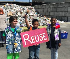 """Three schoolchildren in front of a plastic waste dump in Berkeley, California, campaigning against plastic pollution. Child in the center is holding up a """"reuse"""" sign"""