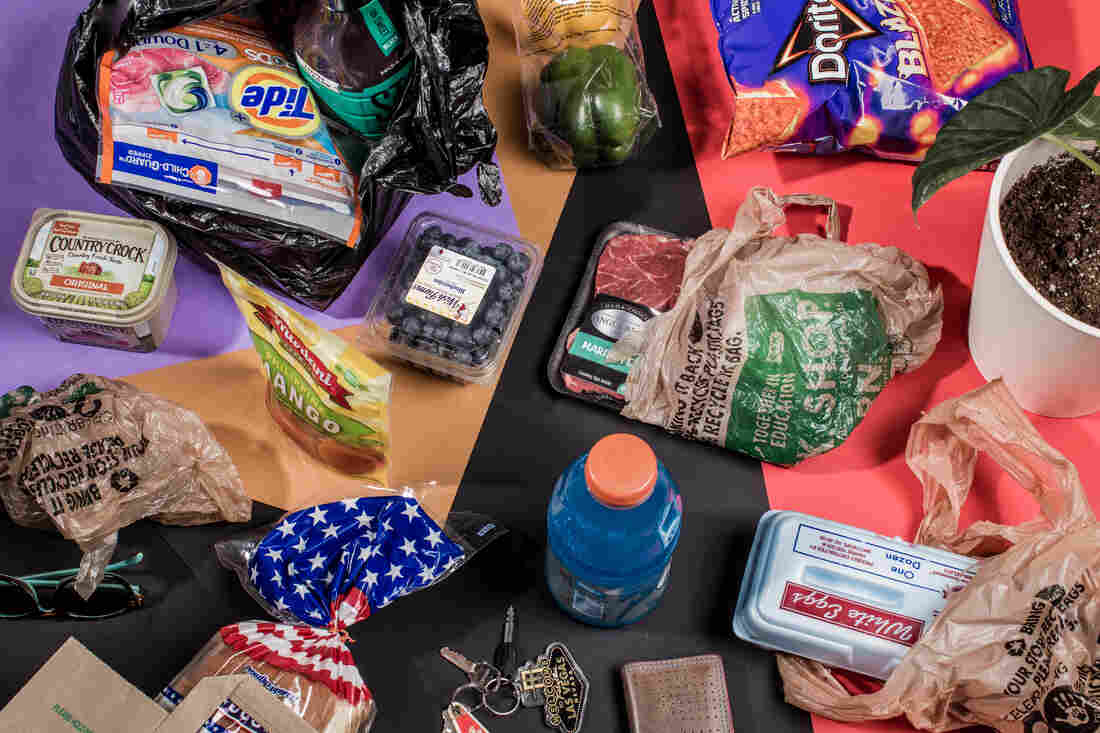 Plastic items including drink bottles, plastic bags and food packaging are strewn about atop a bold purple and red backdrop and photographed from above.