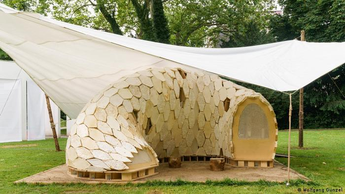 A pod-like small structure under a tent in a park