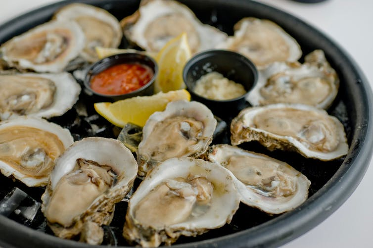 a dish of oysters served with sauces and lemon