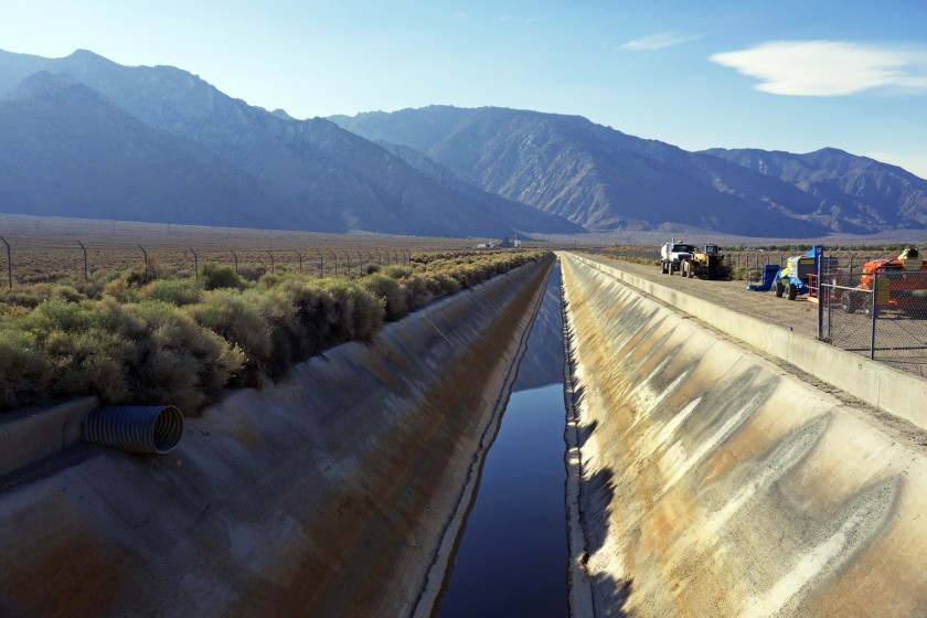 In this Aug. 23, 2015, photo, the Los Angeles Aqueduct has reduced water flow near the eastern Sierra town of Olancha, Calif., after the aqueduct was partially dammed upstream of this area this summer. On Tuesday, Oct. 27, 2015, because of the ongoing drought, water was again flowing south in greater quantities as workers removed the earthen dam that had diverted runoff to the parched Owens Valley. (AP Photo/Brian Melley)