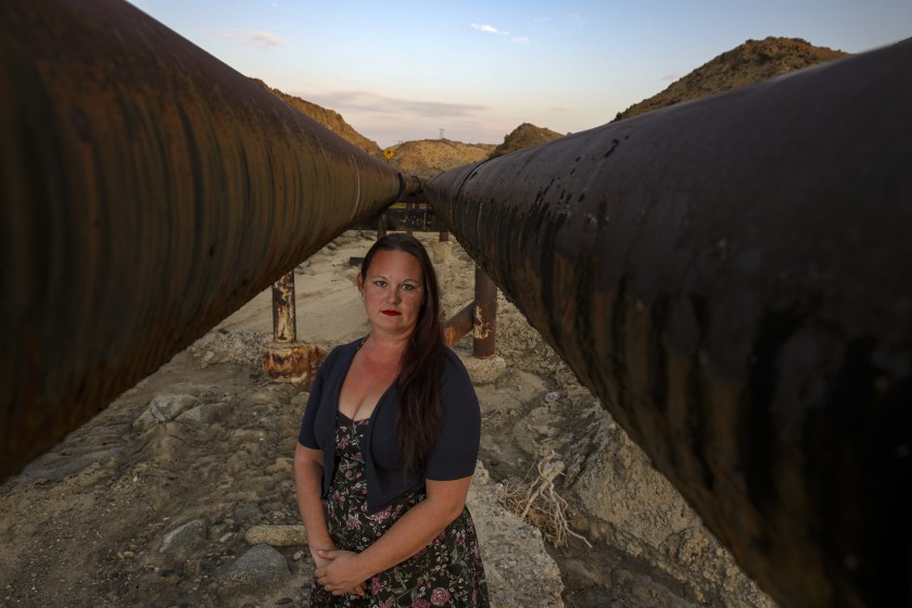 Trona, CA - July 29: Community activist Regina Troglin stands between two rust spotted water pipes, owned by Searles Valley Minerals, traveling through Poison Canyon that supplies water to Trona. Photographed on Thursday, July 29, 2021 in Trona, CA. (Irfan Khan / Los Angeles Times)