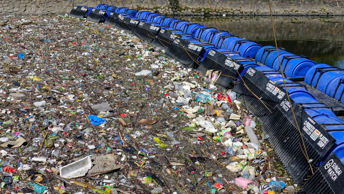 A Walker Barrier comprised of plastic drums holds back one day's worth of trash